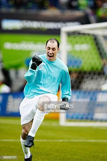 Soccer goalkeeper celebrating on field
