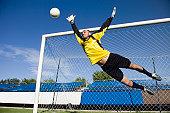 A soccer goalkeeper diving to block a shot