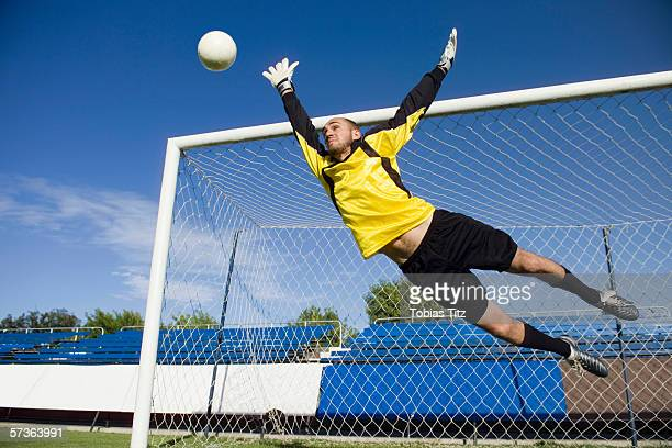A soccer goalkeeper diving to block a shot