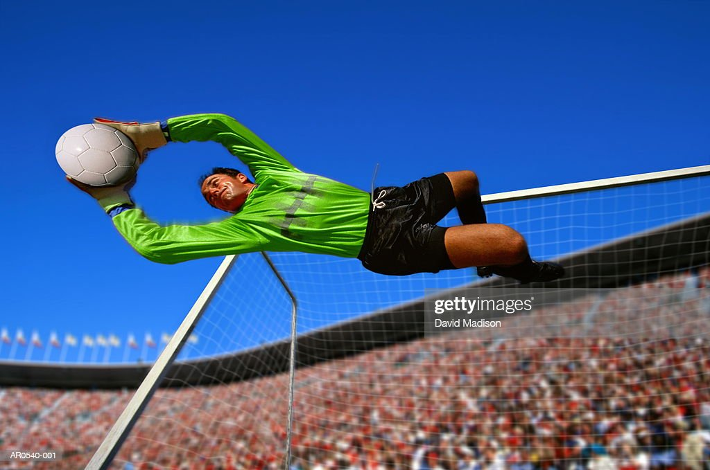 Soccer goalkeeper diving with ball in stadium (Digital Composite) : Stock Photo
