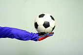 Soccer goalkeeper holding soccer ball on gray background.