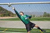 Soccer goalkeeper reaching for ball