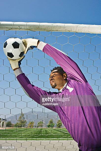 Soccer goalkeeper reaching for ball