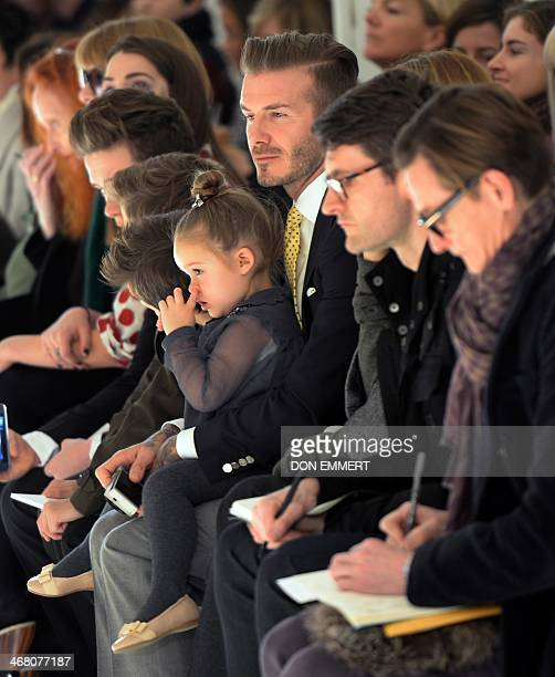 Soccer great David Beckham with his daughter Harper look on as models present the fashions of Victoria Beckham during the MercedesBenz Fashion Week...