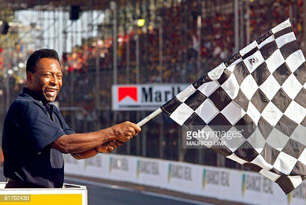 Soccer legend Edson Arantes do Nascimento known as 'Pele' waves the final flag to German Formula One World Champion Michael Schumacher at the...