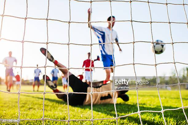 Soccer match from the goalkeeper's net.