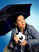 Soccer mom holding umbrella