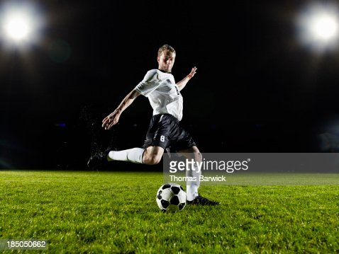Soccer player about to kick ball on field