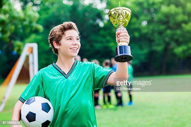 Soccer player admires trophy