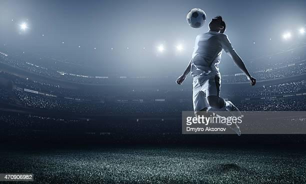 A soccer player at a stadium mid air kicking a ball