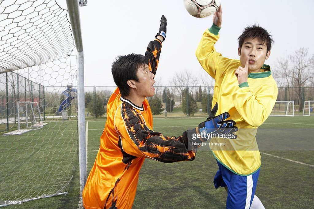 Soccer player attempts to cheat by throwing the ball into the goal : Stock Photo
