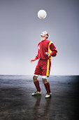 Soccer player bouncing soccer ball on head
