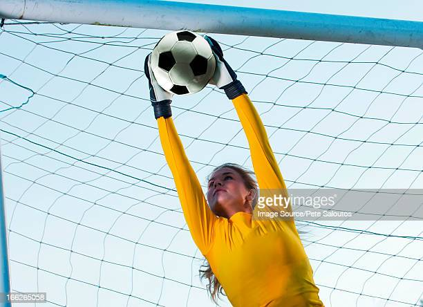 Soccer player catching ball in goal