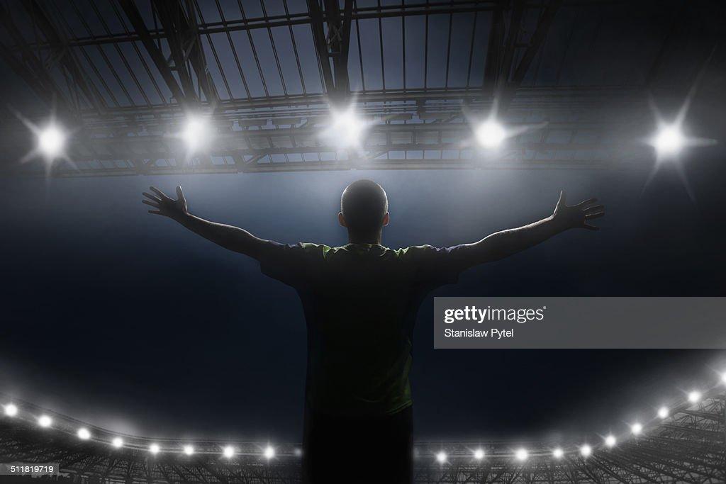 Soccer player celebrating victory in stadium
