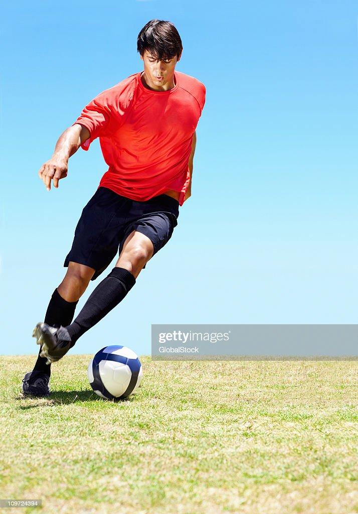Soccer player dribbling a ball on the field : Stock Photo