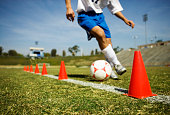 Soccer Player Dribbling Around Orange Cones