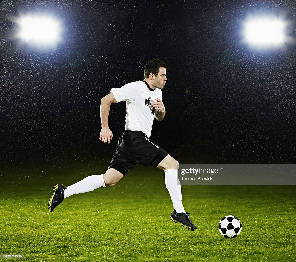Soccer player dribbling ball down field