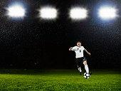Soccer player dribbling ball on field in rain