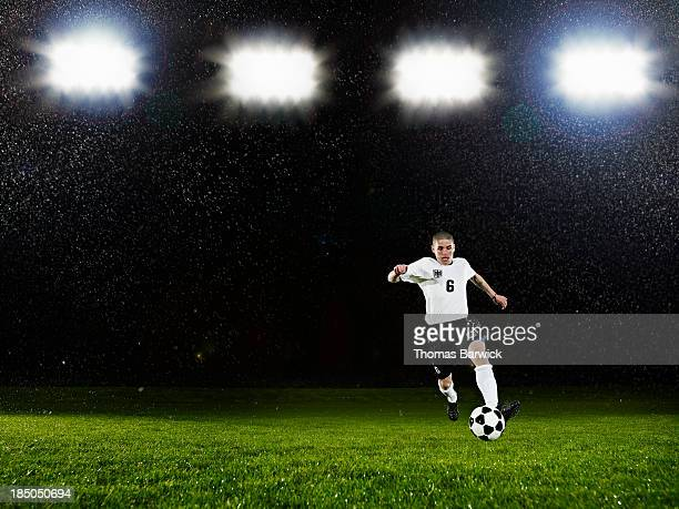 Soccer player dribbling ball on field in rain