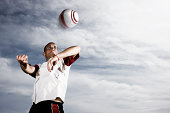 Soccer Player Heading Ball Against Stormy Sky