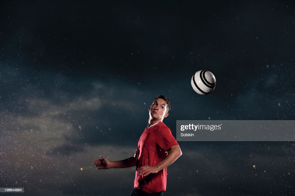 soccer player heading ball in rainy weather : Stock Photo