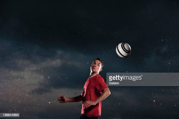 soccer player heading ball in rainy weather