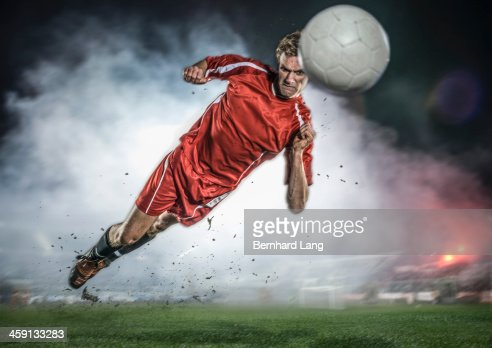 Soccer player heading ball in stadium