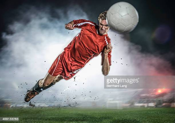 Soccer player heading ball in stadium