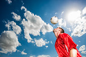 Low angle view of soccer player practicing and heading the ball against the sky.