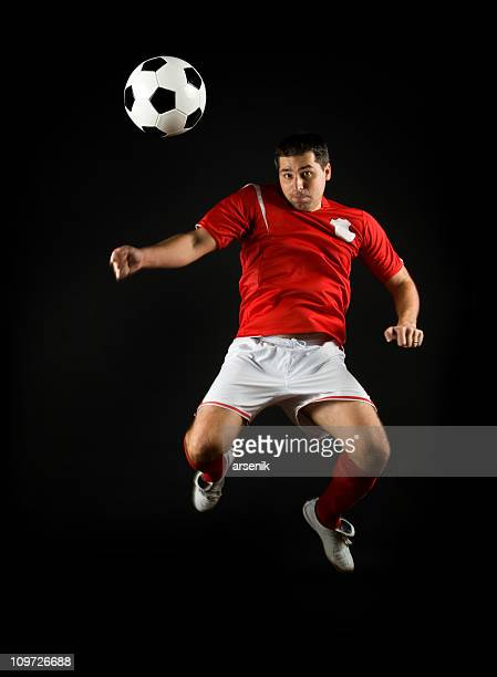 Soccer Player Heading the Ball, Isolated on Black