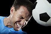 Soccer player heading the soccer ball against black background