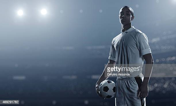 Soccer player holding ball in stadium