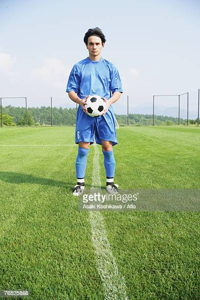 Soccer player holding ball on touchline