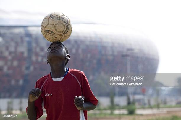 A soccer player in a youth team practice on a field in front of Soccer City on January 16 in Johannesburg South Africa This young player practice...