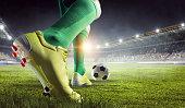Soccer player at stadium kicking ball. Mixed media