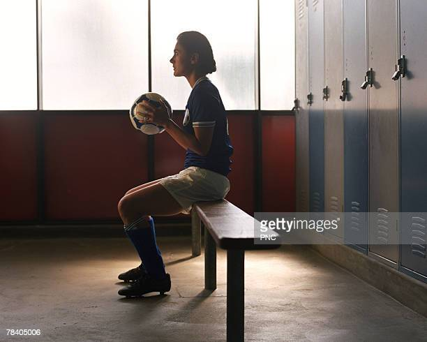 Soccer player in locker room preparing for game