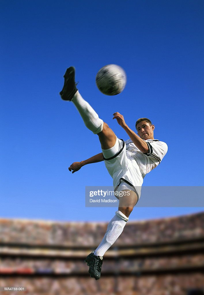Soccer player in mid air, kicking ball : Stock Photo