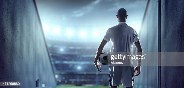 Soccer player in players zone of a stadium