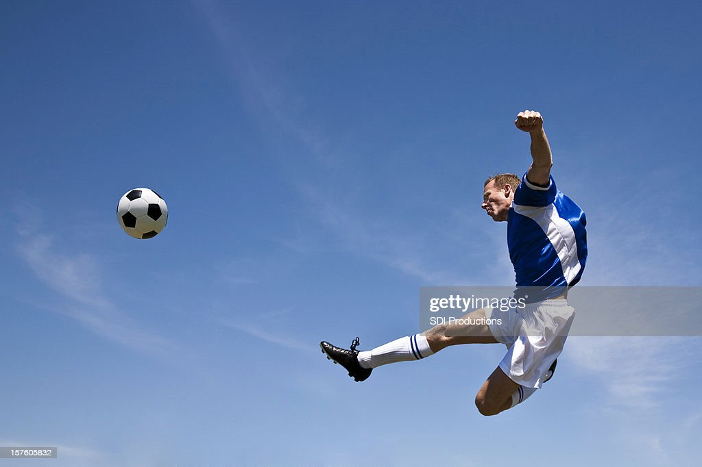 Soccer Player in the Air Kicking Ball