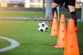soccer player jogging with trap and control football between cone markers for football training.