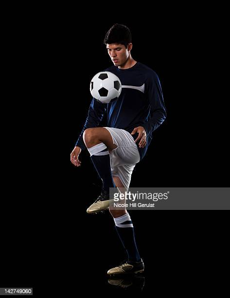 Soccer player juggling the ball.