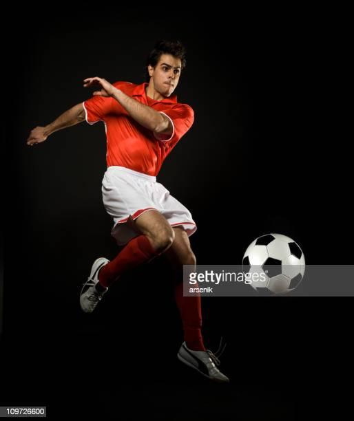 Fußball Spieler-Jumping in Air mit Ball, isoliert auf Schwarz