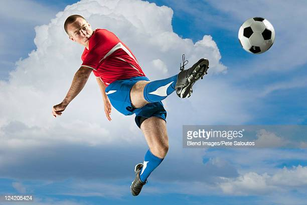 Soccer player jumping in mid-air kicking ball