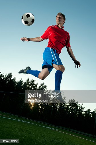 Soccer player jumping in mid-air kicking ball : Stock Photo