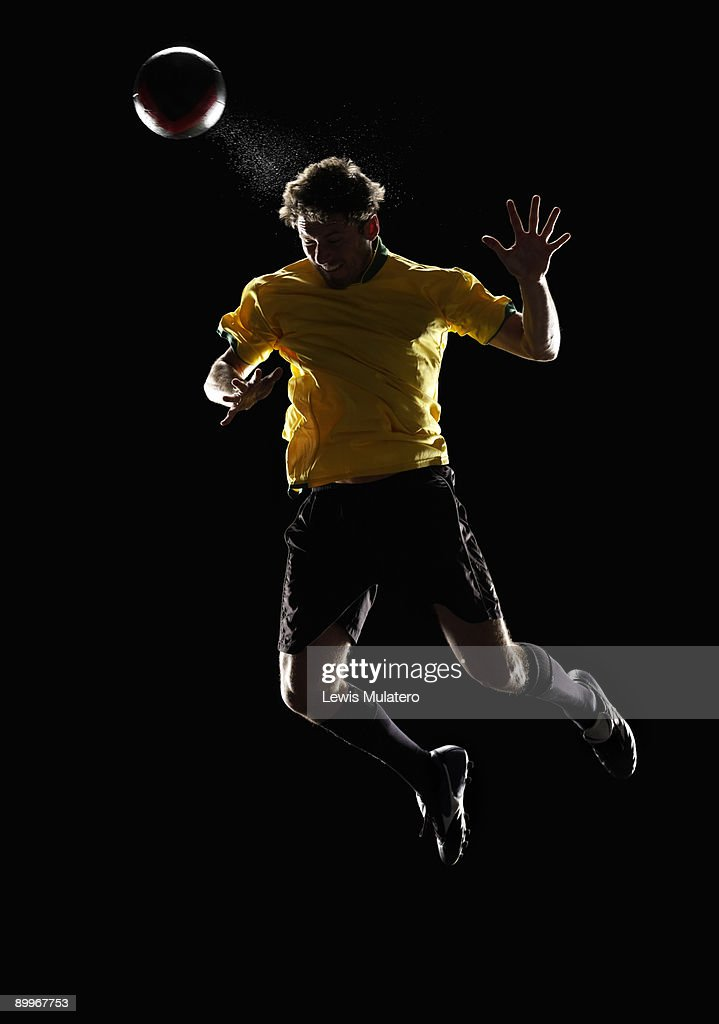 Soccer player jumping in the air to head a ball : Stock Photo