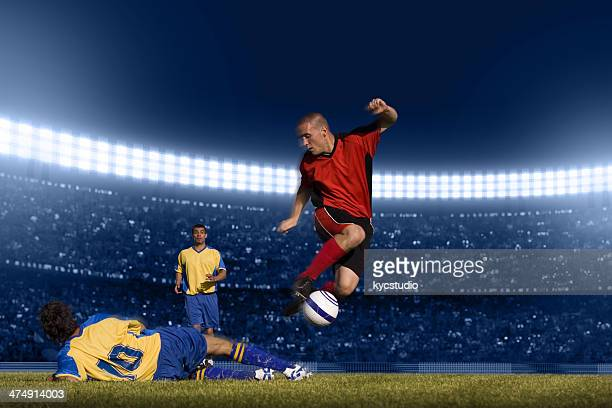 Soccer player jumping with ball
