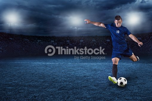 Soccer player kicking ball in a large stadium at night