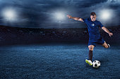 Action photo of professional soccer or football player during game in full floodlit stadium at night