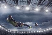 Soccer player kicking ball in air at stadium
