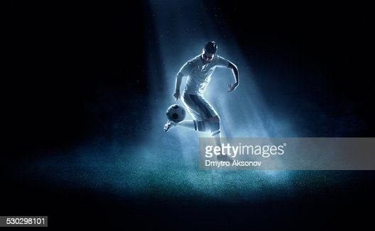 Soccer player kicking ball in spotlight
